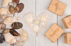 grupo de shell, de pérolas apresentados na forma do coração e de caixas de presente do mar no fundo de madeira branco Fotos de Stock Royalty Free