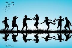 Grupo de siluetas de los niños que juegan cercano al aire libre Imagenes de archivo