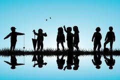 Grupo de siluetas de los niños que juegan cercano al aire libre Fotografía de archivo libre de regalías