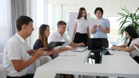 Grupo de socios comerciales en la reunión que discuten trato en la tabla en el trabajo en la sala de reunión metrajes