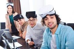 grupo de socios comerciales multiétnicos con las auriculares de la realidad virtual en la tabla con los ordenadores portátiles en fotografía de archivo