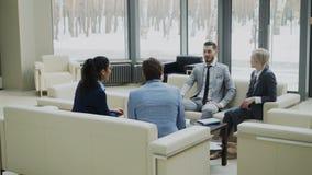 Grupo de socios comerciales que discuten el acuerdo whilesitting en el sofá en pasillo moderno de la oficina con las ventanas pan