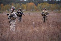Grupo de soldados armados que se colocan en el campo fotos de archivo libres de regalías