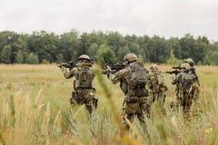 Grupo de soldados que conducen una ofensiva contra el enemigo Foto de archivo