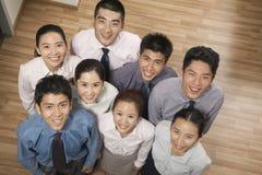 Grupo de sonrisa y compañeros de trabajo felices que miran para arriba la cámara, retrato, tiro de arriba Imagen de archivo
