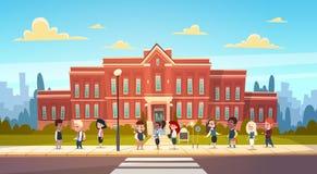 Grupo de soporte de raza de la mezcla de los alumnos en los alumnos de Front Of School Building Primary que hablan a estudiantes Fotos de archivo libres de regalías
