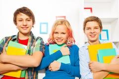Grupo de soporte de tres adolescencias que sostiene los libros de texto Imagenes de archivo