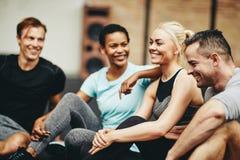 Grupo de sorriso de amigos diversos que sentam-se junto em um gym imagem de stock