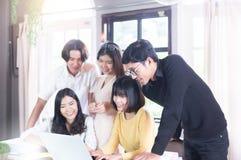 Grupo de sorriso asiático novo e de usar o labtop e de escrever do Freelancer a nota na biblioteca de faculdade fotos de stock royalty free