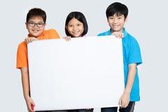 Grupo de sorriso feliz de crianças que mostram a placa vazia do cartaz fotografia de stock royalty free