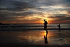 Grupo de Sun da silhueta que funciona na praia Fotos de Stock Royalty Free