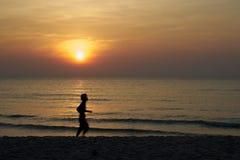 Grupo de Sun no mar da água com ondas e fundo alaranjado do céu da cor Foto de Stock