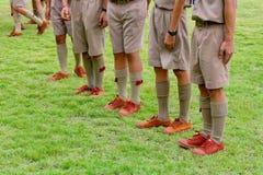 Grupo de suportes tailandeses do boyscout que alinham no campo de futebol da escola para aprender a atividade de acampamento do e imagens de stock