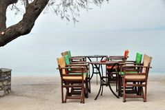 Grupo de tabela e de cadeiras do café que esperam clientes pelo mar Fotos de Stock Royalty Free