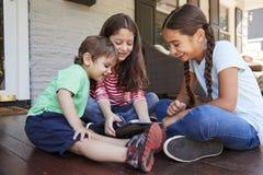 Grupo de tabuleta de Sit On Porch Playing With Digital das crianças imagem de stock royalty free