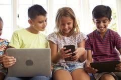 Grupo de tecnologia do uso de Sit On Window Seat And das crianças fotos de stock