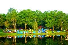 Grupo de tienda de campaña de la gente de la felicidad con el pequeño bosque y el lago foto de archivo