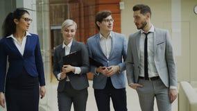 Grupo de tiro de Stedicam de hombres de negocios jovenes que hablan y que caminan en pasillo de la oficina almacen de metraje de vídeo