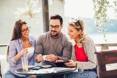 Grupo de três amigos que têm o divertimento um café junto foto de stock royalty free
