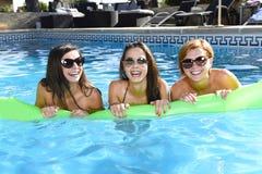 Grupo de três felizes e amigos de moça bonitos que têm o bastão Imagem de Stock Royalty Free