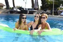 Grupo de três felizes e amigos de moça bonitos que têm o bastão Imagens de Stock Royalty Free
