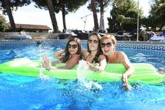 Grupo de três felizes e amigos de moça bonitos que têm o bastão Fotografia de Stock