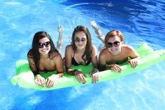 Grupo de três felizes e amigos de moça bonitos que têm o bastão Fotografia de Stock Royalty Free