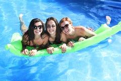 Grupo de três felizes e amigos de moça bonitos que têm o bastão Fotos de Stock Royalty Free