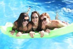 Grupo de três felizes e amigos de moça bonitos que têm o bastão Foto de Stock