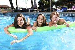 Grupo de três felizes e amigos de moça bonitos que têm o bastão Imagens de Stock
