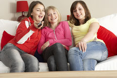Grupo de três meninas que prestam atenção à tevê Foto de Stock
