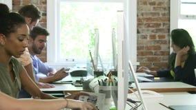 Grupo de trabajadores en los escritorios en oficina conceptora ocupada almacen de video