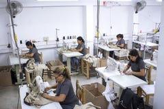 Grupo de trabajadores peruanos con la máquina de coser que hace alteraciones a la ropa fotos de archivo