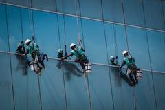 Grupo de trabajadores que limpian servicio de las ventanas en el alto edificio de la subida Imágenes de archivo libres de regalías