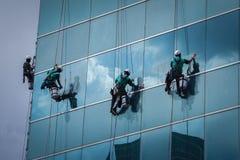 Grupo de trabajadores que limpian servicio de las ventanas en el alto edificio de la subida Fotografía de archivo libre de regalías