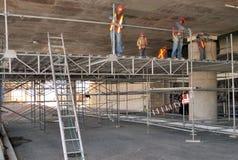 Grupo de trabajadores que montan el andamio en su espacio de trabajo fotografía de archivo
