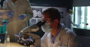 Grupo de trabajo de los científicos en laboratorio de la microbiología almacen de metraje de vídeo