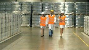 Grupo de trabalhador que move-se através do armazém video estoque