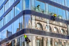 Grupo de trabalhadores que limpam o serviço das janelas na construção alta da elevação fotos de stock