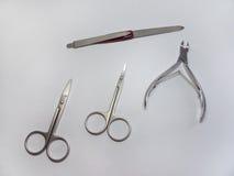 Grupo de tratamento de mãos: pinça do prego, tesouras retas; tesouras da cutícula (tesouras do prego dobradas) e nailfile Fotos de Stock Royalty Free
