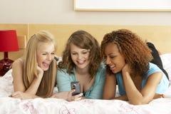 Grupo de tres adolescentes que usan el teléfono móvil adentro Foto de archivo libre de regalías