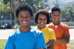 Grupo de tres adultos jovenes afroamericanos de risa con los brazos cruzados Fotos de archivo