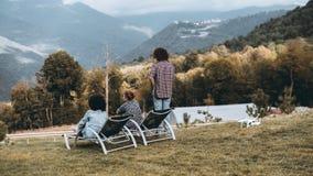 Grupo de tres amigos observando tierras de la colina foto de archivo