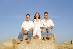 Grupo de tres amigos que se sientan en una bala de la paja Imagen de archivo libre de regalías