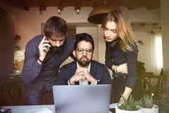 Grupo de tres compañeros de trabajo jovenes que trabajan en el lugar moderno en el ordenador portátil móvil en la tabla de madera fotografía de archivo libre de regalías