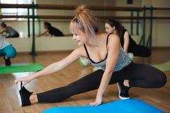 Grupo de tres muchachas que hacen ejercicios en el gimnasio imagen de archivo