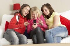 Grupo de tres muchachas que leen el mensaje de texto imagen de archivo