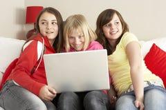 Grupo de tres muchachas que usan la computadora portátil en el país Foto de archivo libre de regalías