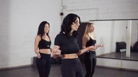 Grupo de tres mujeres atractivas que aprenden movimientos básicos del bachata metrajes