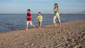 Grupo de tres niños que corren en la playa en el centro turístico de Egipto, m lento almacen de video